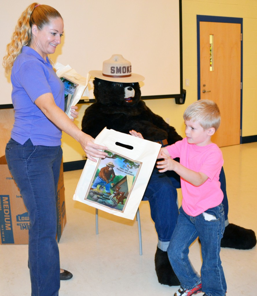 The Delaware Forest Service's  Ashley Peebles hands a Smokey gift bag of school supplies to kindergarten student Paul Bonavita after he pledges to Smokey Bear that he will never play with matches.  He was one of an estimated 535 kindergarten students who participated in the fire prevention program at McIlvaine Early Childhood Center in Magnolia, the largest program in the First State.