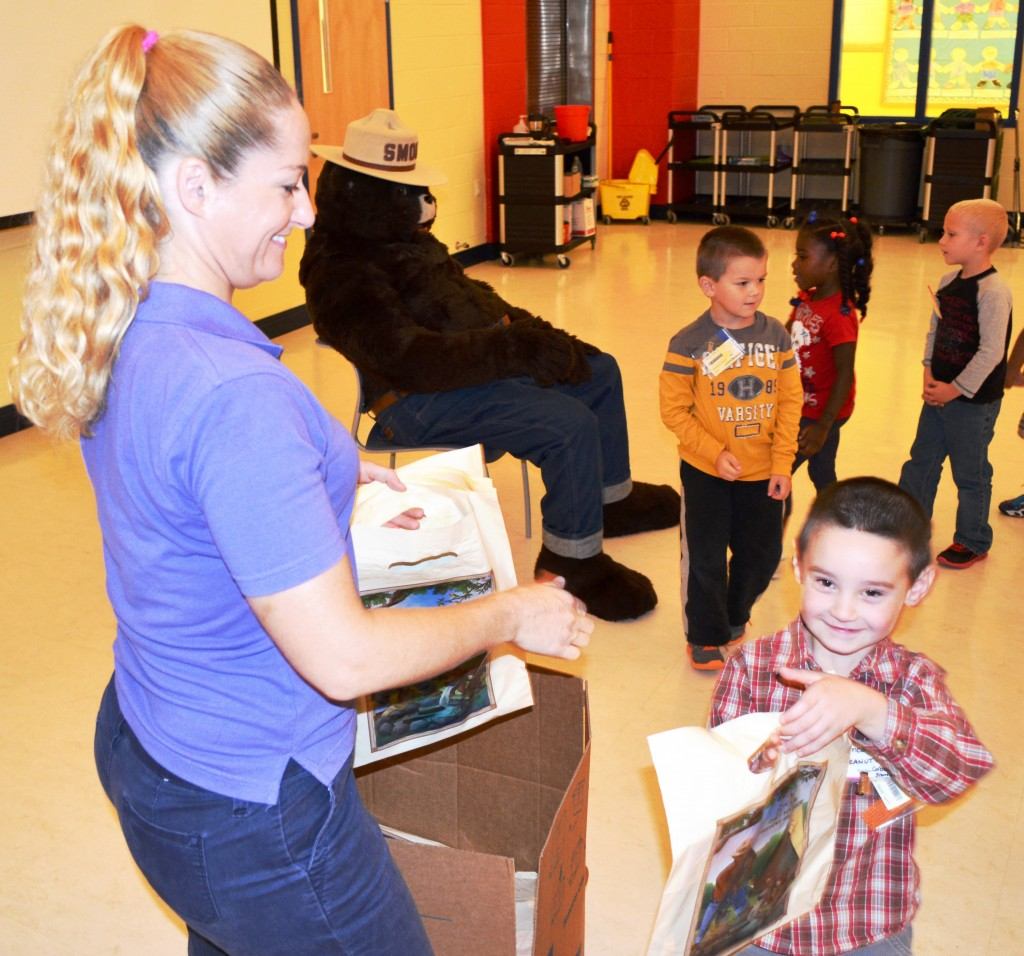 Delaware Forest Service Education Coordinator Ashley Peebles hands a gift bag of Smokey Bear school supplies to James Callis, one of 535 kindergarten students at McIlvaine Early Childhood Center in Magnolia that participated in the annual fire safety and prevention program featuring Smokey Bear.