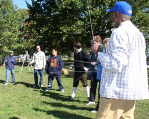 Visitors participating in a Swordmasters fencing demonstration.