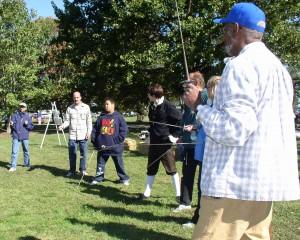 Visitors participating in a Swordmasters fencing demonstration.