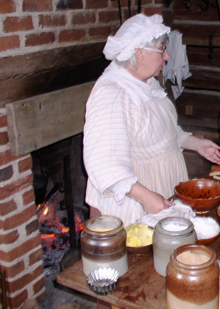 Historic-site interpreter Barbara Carrow conducting a hearth-cooking demonstration in the John Dickinson Plantation's log'd dwelling.