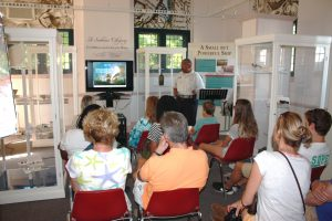 "Visitors listening to a lecture on DeBraak at the Zwaanendael Museum. Sections of the exhibit ""A Seaborne Citizenry: The DeBraak and Its Atlantic World"" are on display in the room."