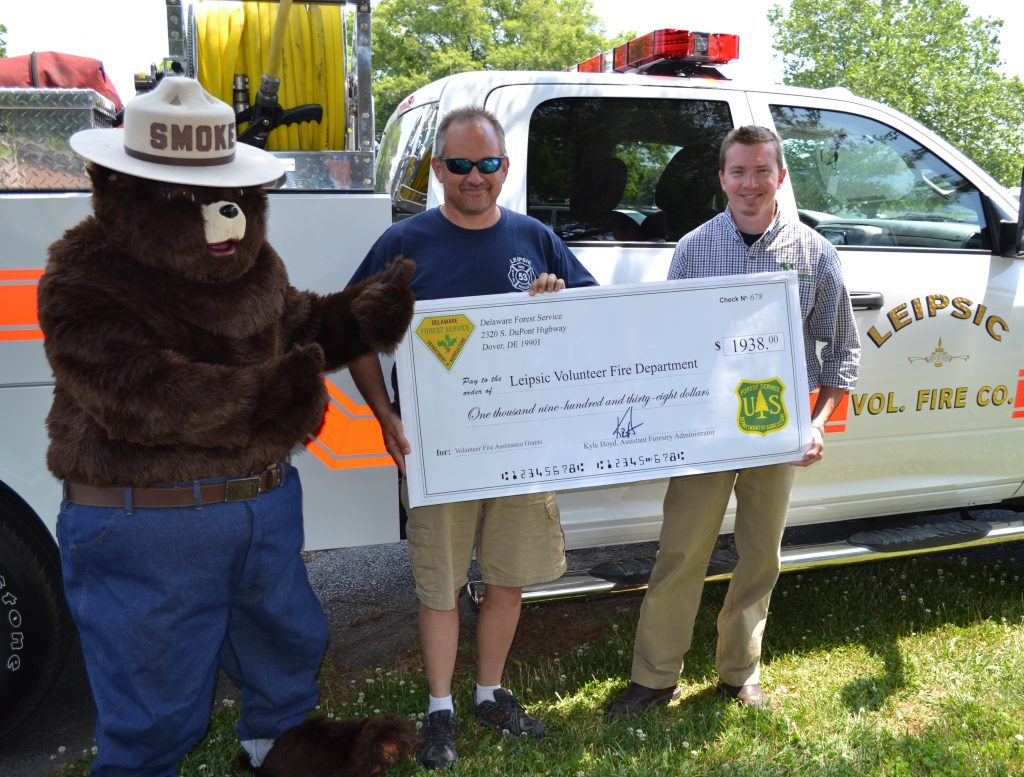 From left, Smokey Bear joined Leipsic Volunteer Fire Company's chief Mike Greco as he accepted a $1938 grant from the Delaware Forest Service's Kyle Hoyd, who administers the agency's wildland fire program. The check is part of a matching grant program to help volunteer fire companies purchase tools and equipment to fight wildfires in their communities.