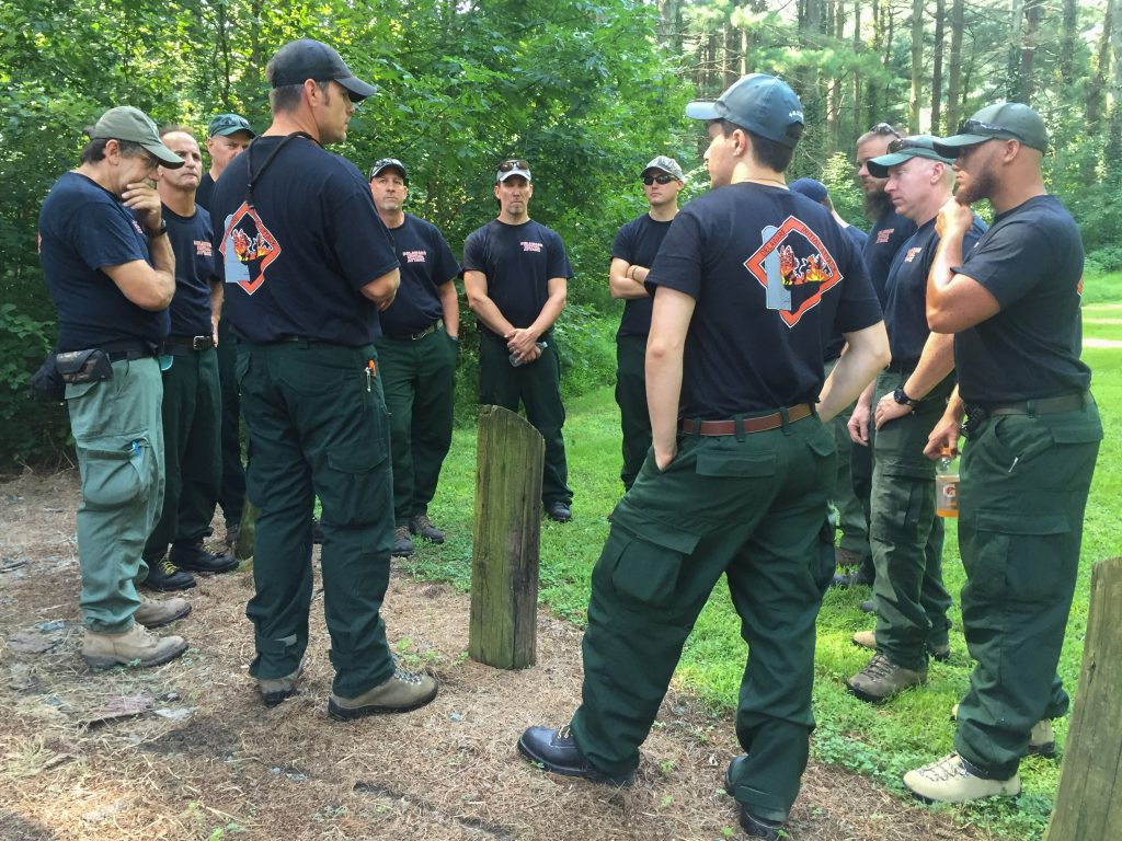 The wildfire crew members listen to their operational briefing from crew boss Erich Burkentine of Milton, a regional forester with the Delaware Forest Service.