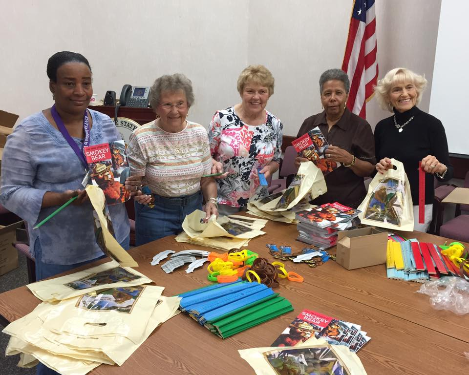 Volunteers from the Dover Modern Maturity Center prepared more than 6,000 bags of Smokey Bear school supplies for schoolchildren.