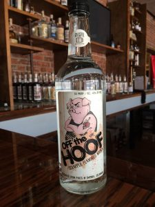 """Showroom at the Painted Stave Distillery with a bottle of one of the company's products—""""Off the Hoof"""" scrapple-flavored vodka."""