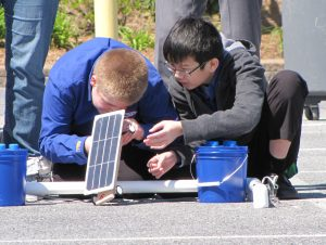Team members work on their solar car at Delaware's 2016 Junior Solar Sprint.