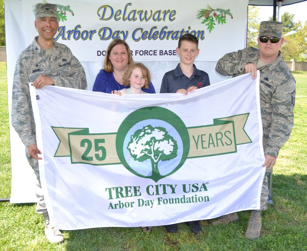 Col. Randy Boswell, 436th Mission Support Group commander, holds the Tree City USA flag with Master Sgt. Donald Bourne, 736th Aircraft Maintenance Squadron airframe powerplant general section chief, and his family April 28, 2017, at Dover Air Force Base, Del. Bourne's daughter, Audriana, won the Kindergarten-level for Kent County in an Arbor Day poster contest. (U.S. Air Force photo by Senior Airman Zachary Cacicia)