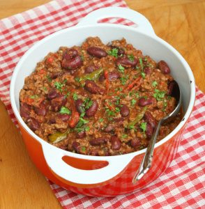 Think Stock Photo of Chilli con carne with ground beef in enameled casserole dish.