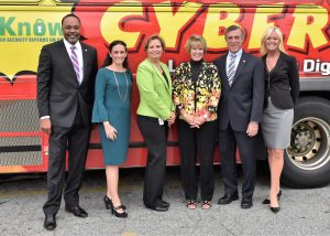 CIO James Collins, DTI; Christine Parker, NSA; Deputy Secretary of Education Karen Field Rogers, DOE; CSO Elayne Starkey, DTI, Governor John Carney; and Kim Paradise, LifeJourney, take a photo in front of a DART bus promoting cyber security.