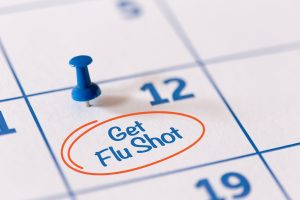 The words Get Flu Shot written on a Calendar