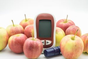 Picture of glucose meter and lancelet surrounded by fresh apples