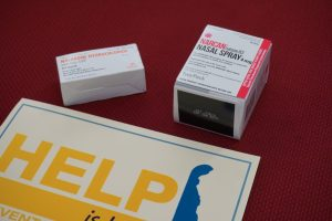 Two boxes of Naloxone above the Help Is Here sign
