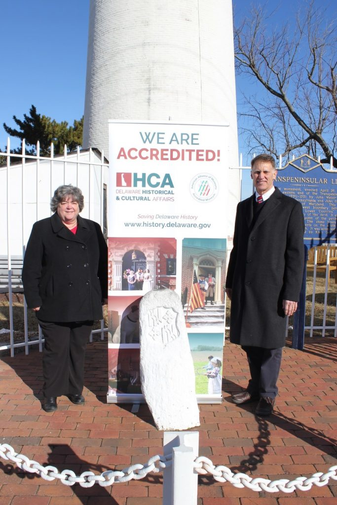 State Rep. Ronald Gray visits the Fenwick Island Lighthouse in celebration of the Division of Historical and Cultural Affairs' accreditation by the American Alliance of Museums. At left is division Deputy Director Suzanne Savery. In front of Savery and Gray is the Transpeninsular Line marker which indicates the boundary between Delaware and Maryland.