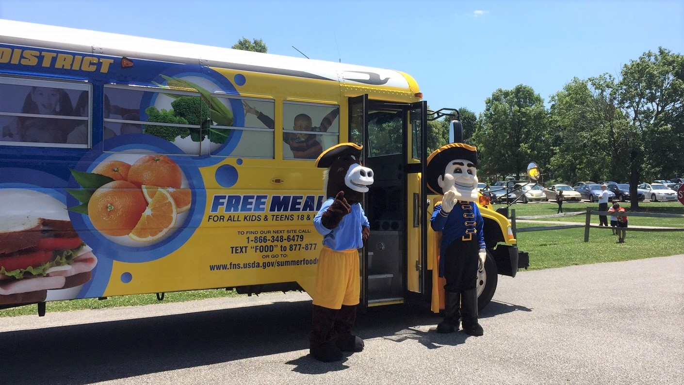 Photo of the Free Meal Bus with Mascots campaign and a bus