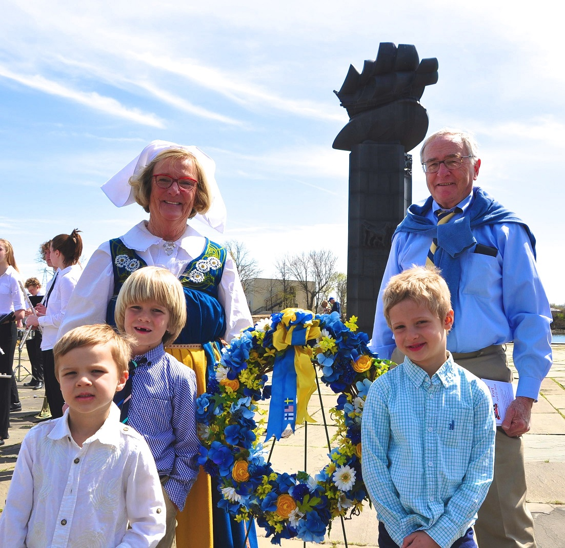 "Elisabeth Hohman of the Delaware Swedish Colonial Society during the ceremony at Fort Christina commemorating the landing of the Swedish colonial vessel, the Kalmar Nyckel, at the site in 1638. With Ms. Homan are (counterclockwise from lower left) her grandsons Kasper, Layton and Gunner Hohman and their grandfather, William Hohman, a volunteer for the Kalmar Nyckel Foundation. The ceremony was part of the foundation's annual ""Festival of the Fort"" which took place on April 22, 2018. In the background is the Swedish Tercentenary Monument which depicts the Kalmar Nyckel."