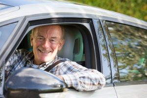 Image of a happy senior driving a car
