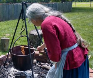 Historic-site interpreter Jennifer Dunham demonstrating how fabric was dyed in the 18th century.