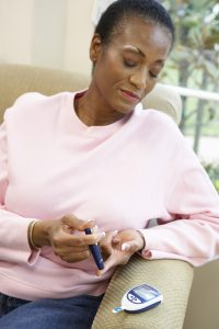 Woman using glucometer to check blood sugar