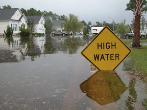 Piture of Neighborhood flooded. Sign warns of high water.