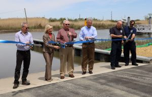 Cutting the ribbon at DNREC's new boat ramp in Little Creek are, left to right: Little Creek Mayor Glenn Gauvry, Lt. Governor Bethany Hall-Long, State Representative William J. Carson Jr., DNREC Secretary Shawn M. Garvin, Little Creek Volunteer Fire Company Chief Michael Scott Bundek, and Little Creek Volunteer Fire Company President Kenneth Frazier. DNREC photo by Joanna Wilson.