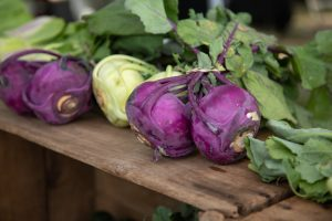 purple and green kohlrabi bulbs on wood crates at farmers' market