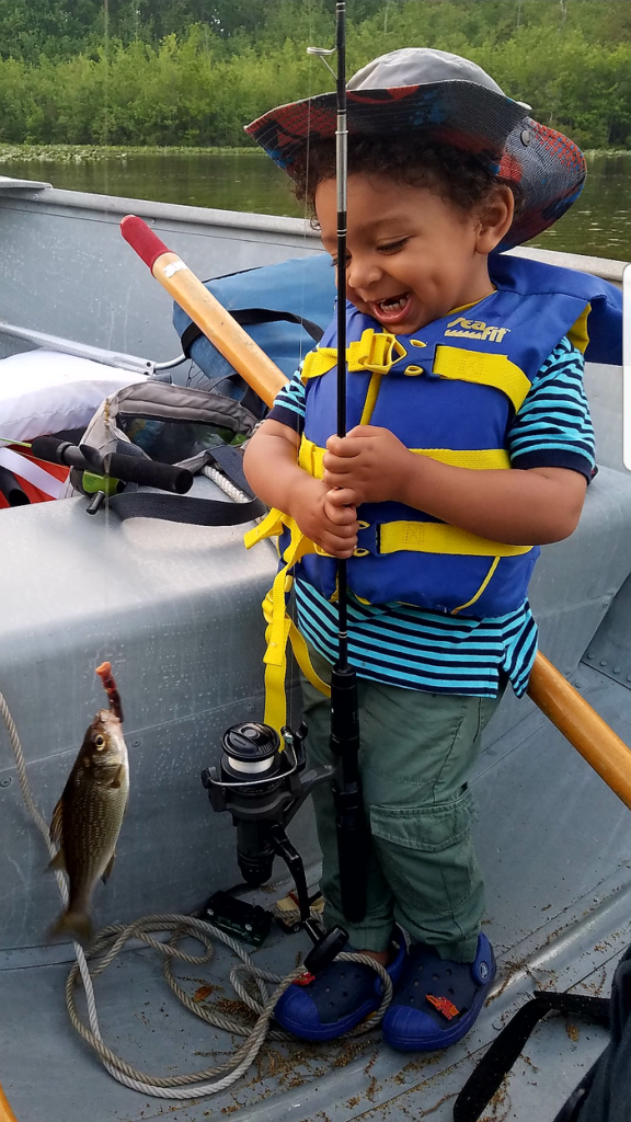 A happy child catches a fish