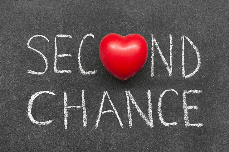 Photo of second chance phrase handwritten on blackboard with heart symbol instead of O