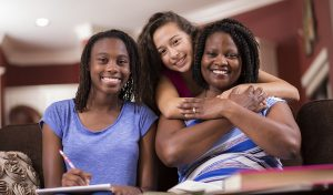 Photo of Multi-ethnic family. Latin and African descent teenage girls and their mom in home setting. Single mom helps the girls as they study their homework together in living room. Girl in center is adopted or a foster child. Mixed race, blended families. Hugs.
