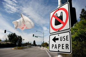 Photo of plastic bag on highway with a sign encouraging using paper bas