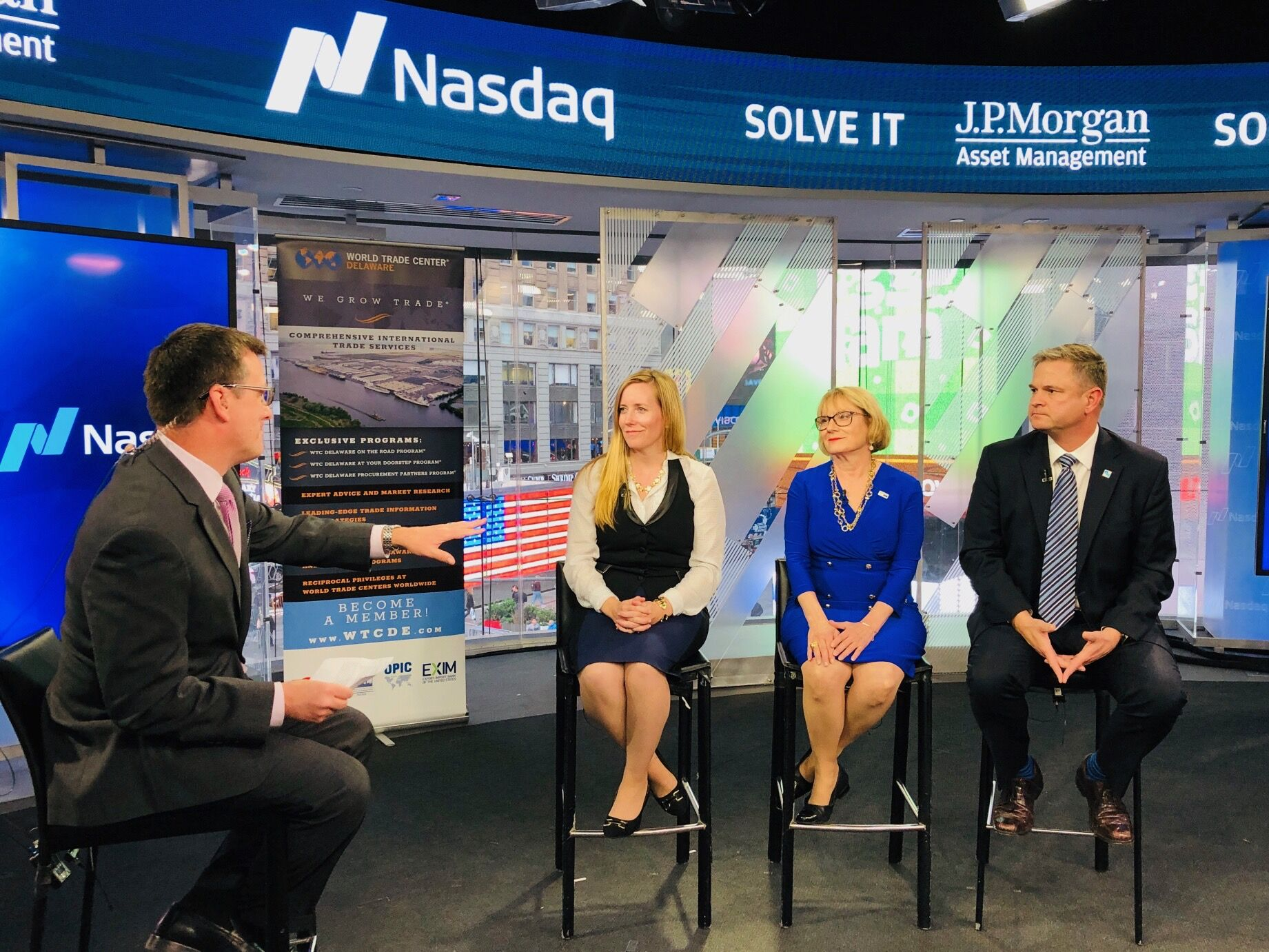 Seated under a Nasdaq banner are State Treasurer Colleen Davis, Carla Sydney Stone, and Dave Harriss. They are being interviewed by Rob Phillips