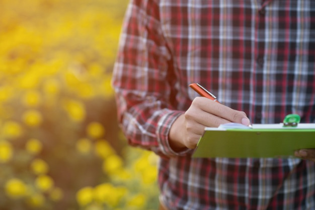 farmer in field with clipboard writing