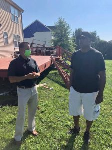 Insurance Commissioner Trinidad Navarro speaking to a resident whose deck was damaged by the storm.