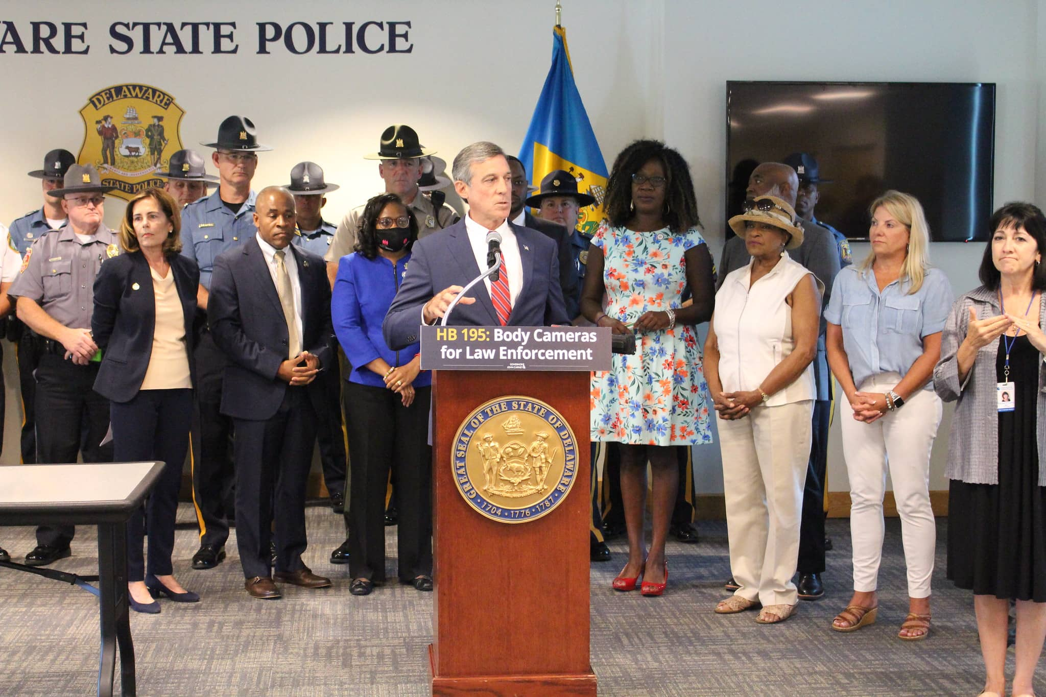 Governor Carney stands at a podium and is surrounded by legislators, law enforcement and advocates.
