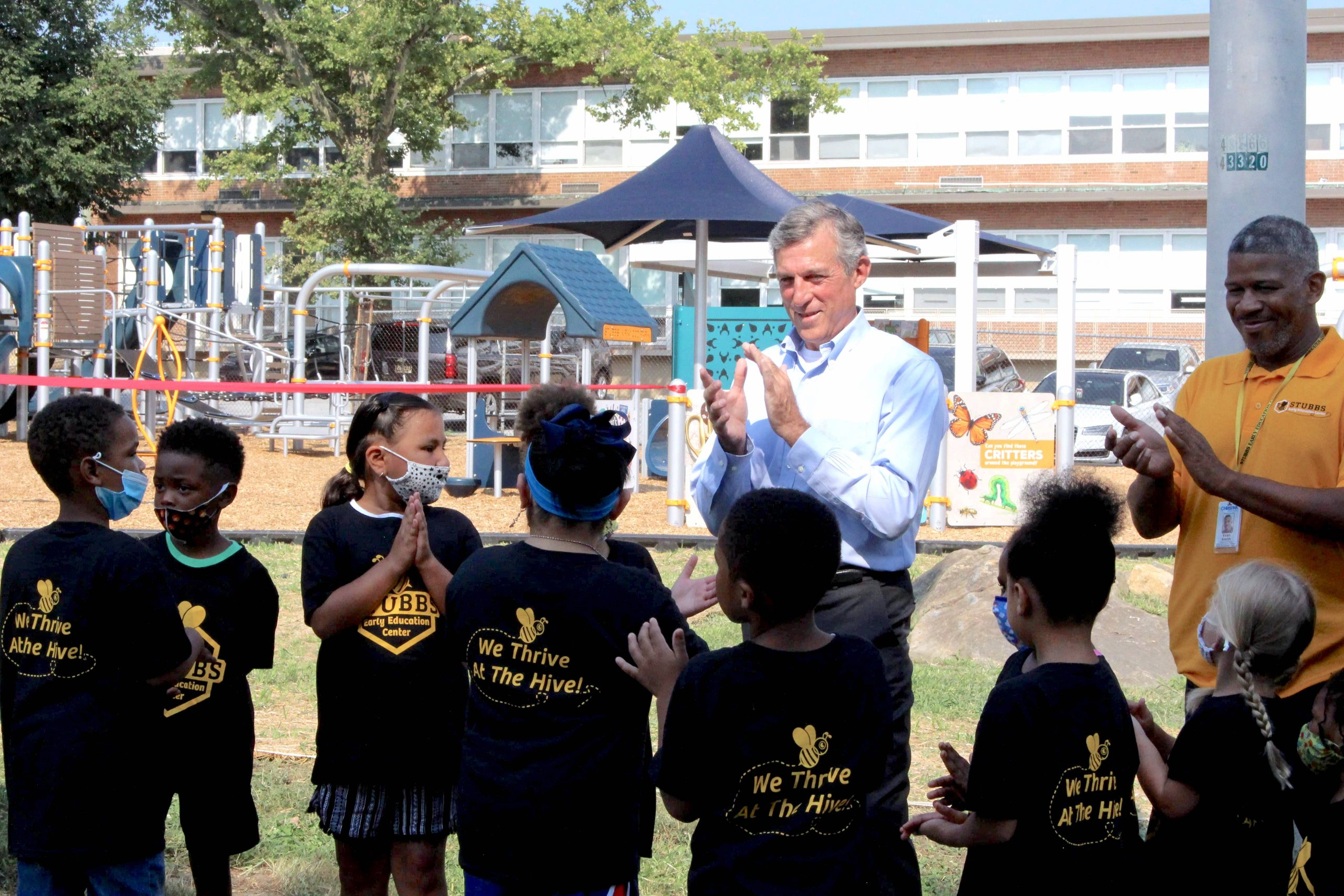 Governor Carney claps his hands with a group of students in front of a park.