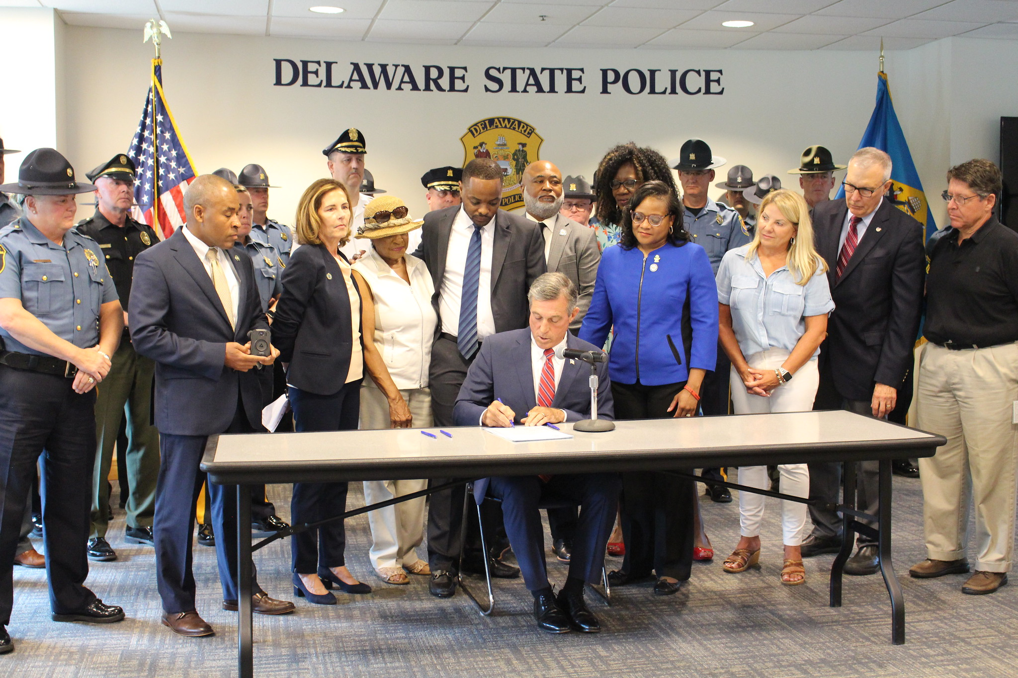Governor Carney signed House Bill 195 while seated at a desk and surrounded by legislators, law enforcement and advocates