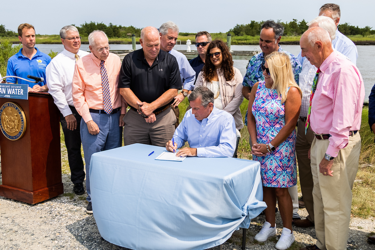 Governor Carney is seated at a table as he signs the Clean Water for Delaware Act. He is surrounded by others who are standing.