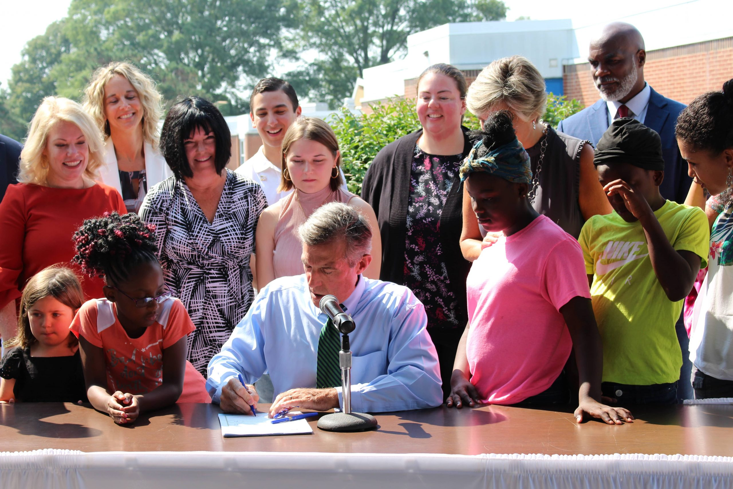 Governor Carney signs House Bill 86 while seated at a table. Legislators and advocates, and students are standing around him.