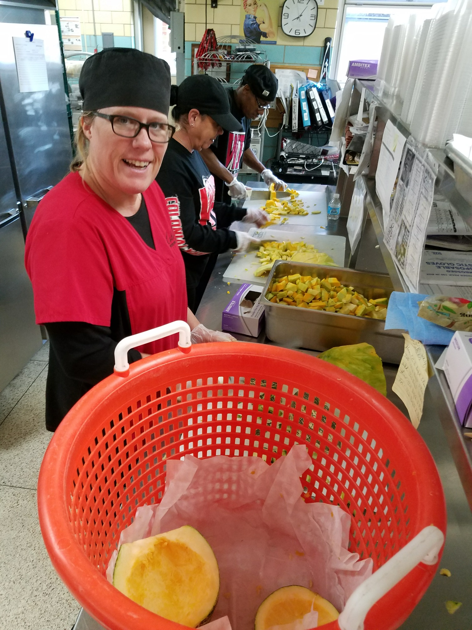 School nutrition worker prepares meals with fresh sqaush