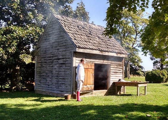 Photo of historic site interpreter Chris Merrill in front of the John Dickinson Plantation's smokehouse