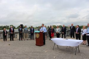 Governor Carney stands behind a podium at a bill signing ceremony event located at a solar array in Wilmington.