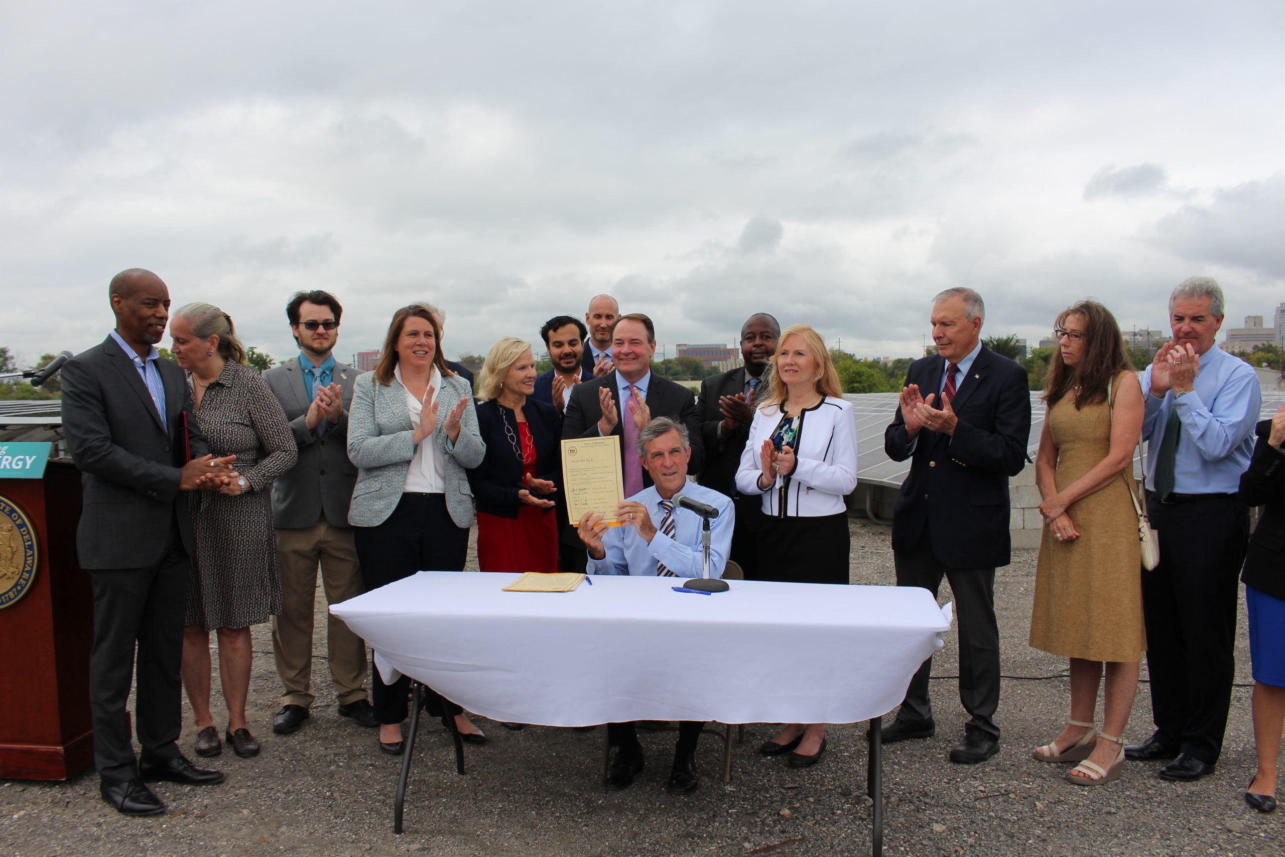 Governor Carney holds up a piece of legislation after signing it into law, surrounded by legislators and supporters, while outdoors at a solar array.