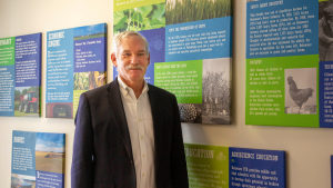 Delaware Secretary of Agriculture Michael T. Scuse stands in the agency lobby in front of colorful panels related to the history of Delaware agriculture.