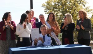 Governor Carney holds up House Bill 123 after signing it into law.