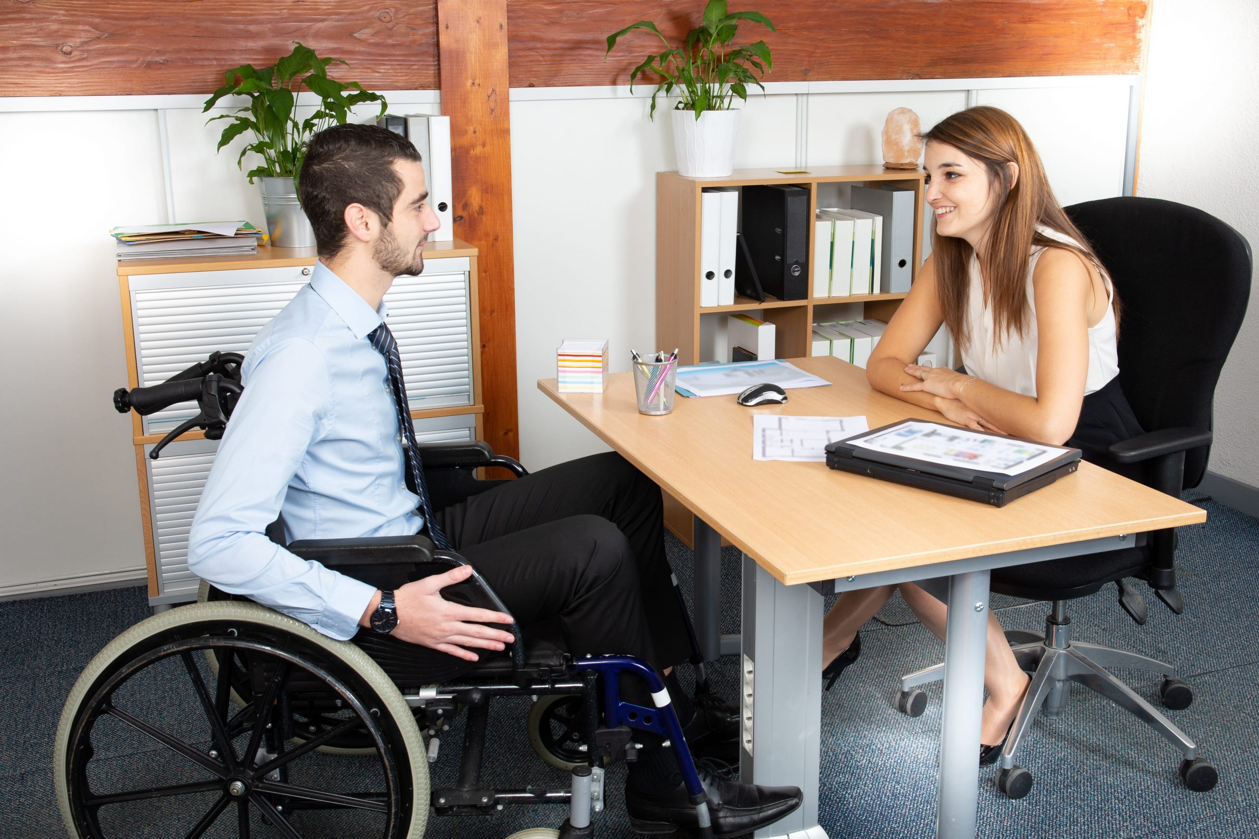 man in wheel chair having a meeting with a woman behind desk.